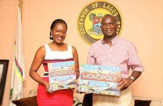 Mrs Nimi Akinkugbe CEO Bestman Games presenting the City of Lagos Edition of Monopoly to Governor Fashola